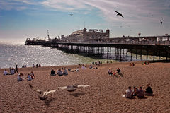 Brighton Pier. Families relax at the seaside beside Brighton Pier in Sussex England Stock Image