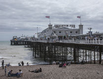 Brighton - the pier and a cloudy sky. This image shows a beach in Brighton, England with some people walking and chilling Stock Photography
