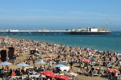 Brighton Pier and crowded beach in Brighton, England Stock Photos