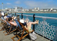 Brighton Pier Palace Pier Brighton Wheel sunbathers. Brighton, United Kingdom - July 4, 2015: Sunbathers relax on deck chairs on Brighton Pier, also known as Royalty Free Stock Photography