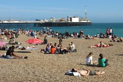 Brighton Pier Palace Pier and sunbathers Brighton England. Brighton, United Kingdom - July 4, 2015: Brighton's pebble beach draws sunbathers on a warm summer Stock Photo