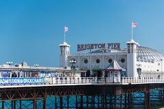 Brighton Pier. View of Brighton Pier from the beach - ads and flags attached on the handrail - Brighton Sussex UK (05/2016 Royalty Free Stock Image