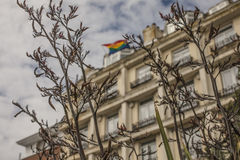 Brighton town - a building and a rainbow flag. This image shows a beach in Brighton, England with some people walking and chilling Royalty Free Stock Image