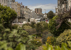 Brighton town - a street with a bench. This image shows a beach in Brighton, England with some people walking and chilling Royalty Free Stock Photos