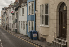 Brighton town - a street. This image shows a beach in Brighton, England with some people walking and chilling Stock Photo