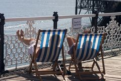 Brighton Two Deckchairs. Relaxing on the deckchairs in Brighton, UK Stock Photos