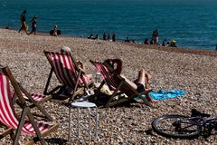 Brighton, UK - June 2018 Couple Relaxing on Wood Adjustable Recliner under the Sun. Family and Group Enjoying Blue Water stock photography