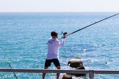 Brighton, UK - June 2018 Man with Cap Standing on Shore Holding Sideways Long Fishing Rod with Reel. Crystal Blue Wavy. Water on Sunny Day. Water Sport Activity stock images