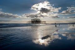 Brighton västra pir på solnedgången med en enslig man som går in i havet Arkivbild