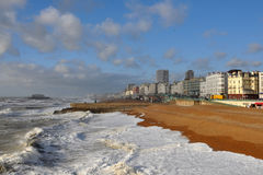 Brighton west beach from pier. Surf running onto Brighton's west beach showing the historic Regency frontage and modern buildings royalty free stock image