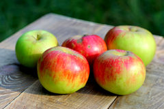 Brights apples on wooden desk board Stock Photos