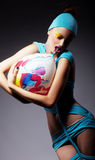 Brignt woman in blue clothing with ball Stock Images