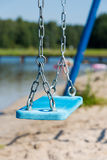 Brigth blue swing in watter park hanged on metal chain Stock Images