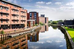 Brik Buildings rosso accanto ad un fiume e ad un cielo blu con le nuvole Fotografia Stock Libera da Diritti