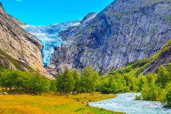 Briksdal glacier, waterfall in Norway. Briksdal or Briksdalsbreen glacier in Olden, Norway with green mountains and river stock photo