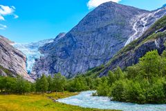 Briksdal glacier, waterfall in Norway. Briksdal or Briksdalsbreen glacier in Olden, Norway with green mountains, river and waterfall stock photography