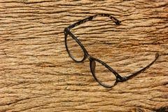 bril op bruine uitstekende houten achtergrond de kortzichtige persoon met bril is aangewezen stock foto