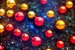 Brilhante e cintilar vermelhos e quinquilharias do Natal do ouro em uma árvore de Natal da pele do pinho fotos de stock