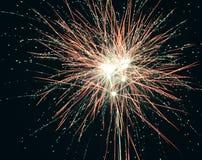 Brilhantemente os fogos-de-artifício explosivos coloridos iluminam acima o céu noturno em celebrações da véspera do ` s do ano no Imagem de Stock