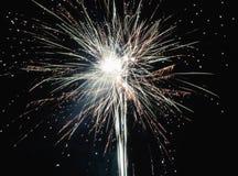 Brilhantemente os fogos-de-artifício explosivos coloridos iluminam acima o céu noturno em celebrações da véspera do ` s do ano no Fotografia de Stock