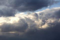 Brilhe do sol entre nuvens de tempestade escuras fotografia de stock