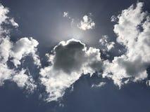 Brilho dos raios de Sun atrás das nuvens brancas Foto de Stock