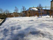 Brilhos da neve nos raios do sol no fundo do encanamento e em casas no inverno ou na mola fotografia de stock royalty free