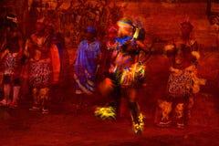 Briljant gekleurde Afrikaanse Danser Abstract in Motie en mensen in Inheems kostuum tegen een geweven rode achtergrond Stock Fotografie