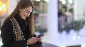 Briljant oostelijk-europian meisje met bruin haar die met haar vriend in reusachtig en mooi winkelcomplex proberen te babbelen stock videobeelden