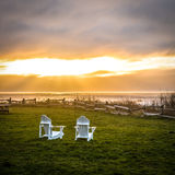 Briljant solnedgång över havet med stolar Fotografering för Bildbyråer