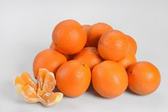 Briljanta orange apelsiner ligger på en hög på en vit bakgrund som lämnas en skalad ny apelsin Arkivfoto