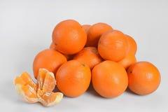 Briljanta orange apelsiner ligger på en hög på en vit bakgrund som lämnas en skalad ny apelsin Royaltyfri Bild