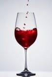 Brillamment le vin rouge a versé dedans le verre à vin pur fragile se tenant sur le fond léger avec la réflexion dedans vers le b Image stock