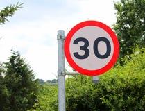 Brillante, limpio, nuevo, muestra 30mph británico del límite de velocidad en el ajuste del país Imagenes de archivo