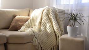 Brillantemente interior elegante de la sala de estar Sofá cómodo de invitación con la manta de lana hecha a mano almacen de metraje de vídeo