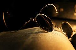 Brille auf Buch Stockbild