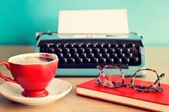 Brillen über Notizbuch, Kaffeetasse und Schreibmaschine Stockbilder