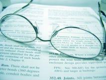 Brillen auf Buch Lizenzfreie Stockfotos