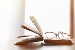 Brillen auf geöffnetem altem Buch Stockbilder