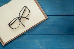Brillen auf geöffnetem Notizbuch Lizenzfreies Stockbild