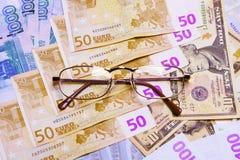 Brillen auf Geldhintergrund Stockbilder