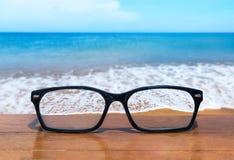 Brillen auf Holztischfront des tropischen Seehintergrundes Lizenzfreies Stockfoto