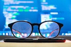 Brillen in der Front weg vom Bildschirm mit Codesyntax Stockbilder