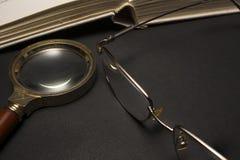 Brillen mit Lupe auf dunkler Oberfläche mit Büchern Stockbild