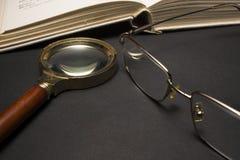 Brillen mit Lupe auf dunkler Oberfläche mit Büchern Stockfotografie