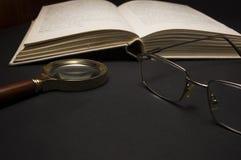 Brillen mit Lupe auf dunkler Oberfläche mit Büchern Lizenzfreies Stockbild