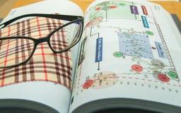 Brillen mit Technikeranalysebuch Stockbilder