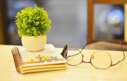 Brillen reservieren und kleine Töpfe auf einem weißen Holztisch Stockbild