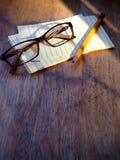 Brillen, Stift und Notizblock Stockfotos