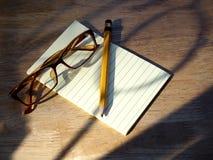 Brillen, Stift und Notizblock Stockfotografie